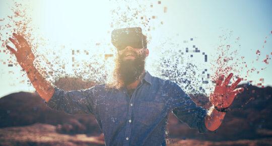 Skäggig kille i öknen bär VR-glasögon och upplöses i pixlar